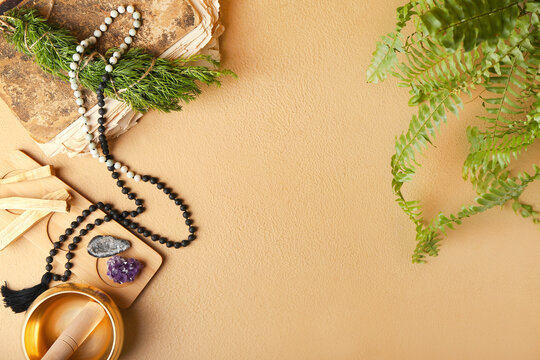 Composition with Tibetan singing bowl, gemstones, beads and Palo Santo on color background
