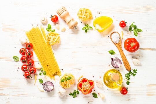 Italian food background on white kitchen table. Raw Pasta, olive oil, spices, tomatoes and basil. Top view with copy space.