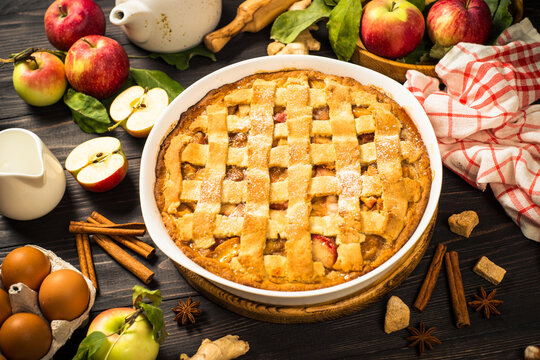 Apple pie with spices at wooden table. Traditional autumn baking with ingredients.