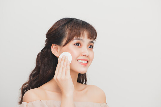 Asian teenager girl cleaning her face with a lotion and a cotton pad