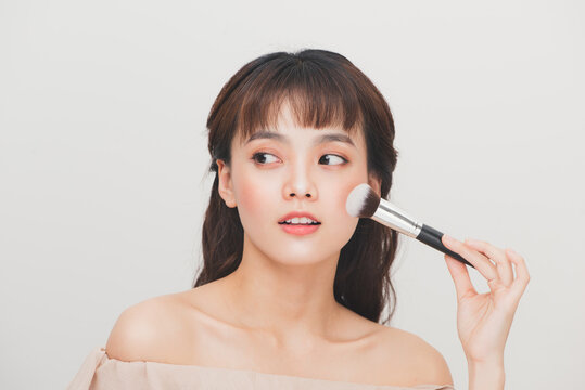Beauty woman applying makeup. Beautiful girl applying cosmetic with a big brush