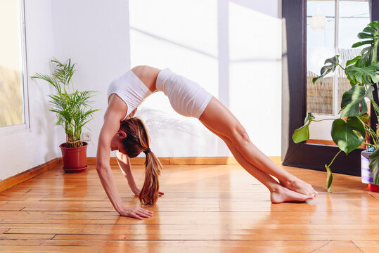 Woman doing yoga in Wheel posture at home