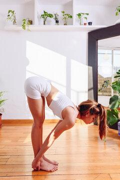 Flexible woman practicing yoga in Halfway Lift pose