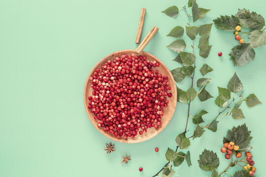 Immune boosting food. Autumn composition with wild cranberries on a wooden plate and hawthorn branches on a mint background with place for text. Natural remedy for immunity and against viruses