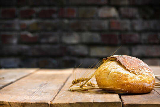 Bakery background. Whole loaf of fresh crispy bread on a wooden table with ears of wheat