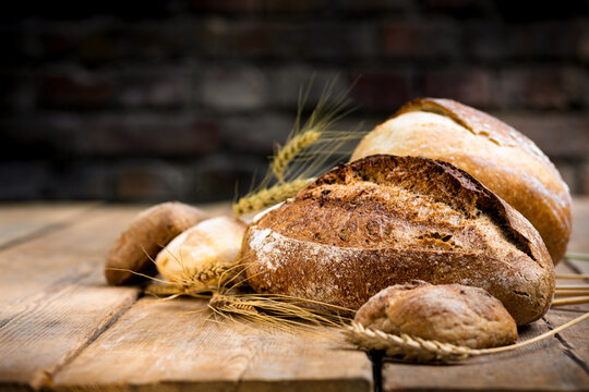 Bakery background. Set of freshly baked crispy bread and buns with ears of wheat on wooden table with copy space