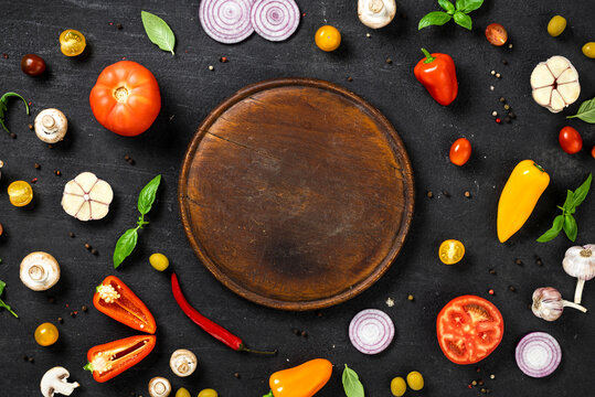 Ingredients for cooking italian homemade pizza with vintage cutting board on black stone background top view