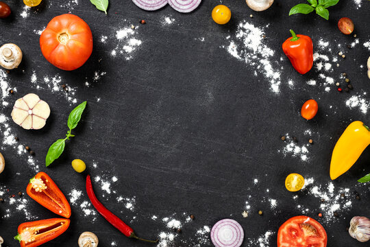 Frame of ingredients for cooking vegetarian homemade pizza on black stone background top view