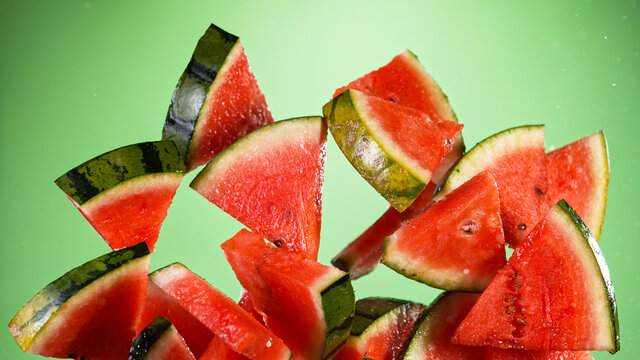 Fresh pieces of water melon flying on green gradient background