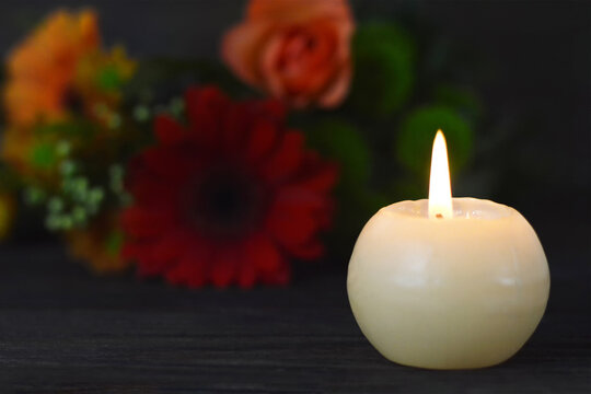 Burning candle and flowers on dark background. Sympathy card