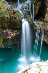 Beautiful image of blurred stream of waterfalls falling over mossy rocks