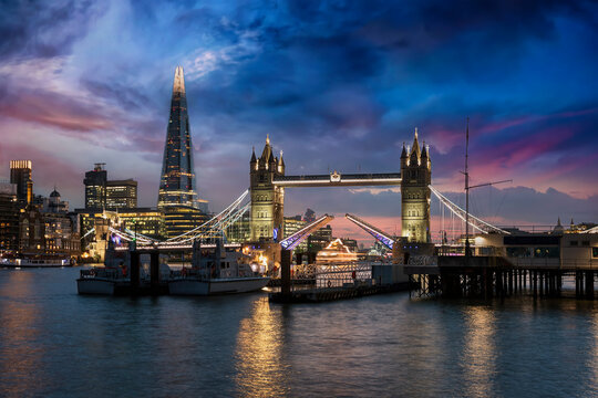 The lifted Tower Bridge and illuminated skyline of London, United Kingdom, during dusk just after sunset