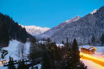 Fototapeta Wieczorny, zimowy krajobraz górski . W dole wioska alpejska. Żółta smuga świateł samochodów. Długi czas naświetlania. obraz