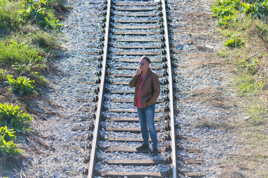 lonely man standing and smoking on railroad tracks