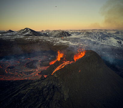 Scenic view of volcano erupting at sunset