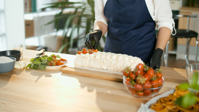 Close-up. The Pastry Chef Puts Fresh Strawberries on a Meringue Cake With Cream. Beautiful Cake Decoration With Cream and Strawberries.