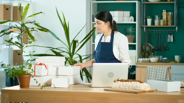Successful Female Small Business Owner Prepares a Customer Order. Modern Designer Kitchen. Confectionery and Favorite Business. Organization of Work in the Field of Delivery. Startup.