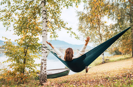 The young woman cheerfully rose arms up while she swinging in a hammock between the birch trees on the mountain lake bank. Out-of-town Outdoor Recreation in Nature concept image.