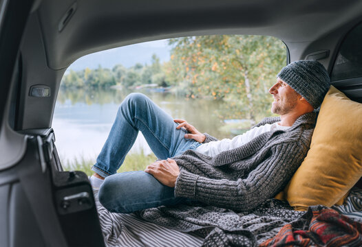 Smiling middle-aged man dressed in warm knitted clothes and jeans lying in the cozy car trunk and enjoying the mountain lake view. Warm early autumn auto traveling concept image.