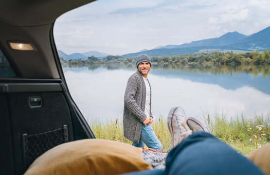Smiling middle-aged man dressed in warm knitted clothes and jeans near the car. Trunk mountain lake view with woman legs in white sneakers. Cozy early autumn couple auto traveling concept image.