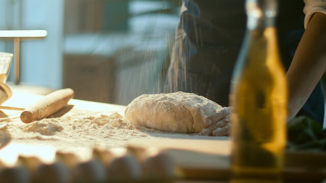 Successful Businesswoman is Happy To Knead the Dough on a Wooden Table in a Cozy Home Kitchen. Woman Baker Enjoys the Process of Making Homemade Cakes. Favorite Work. Small Business.Close-up.
