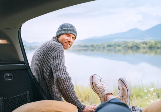 A middle-aged man dressed in warm knitted clothes near the car smiling at a woman in a car trunk who enjoying a mountain lake view. Cozy early autumn couple auto traveling concept image.