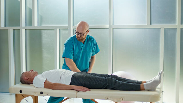 An Adult Man Trains Muscle Strength With a Professional Doctor in a Modern Rehabilitation Clinic. Physiotherapy Program, Rehabilitation After Medical Injuries. Healthcare Concept