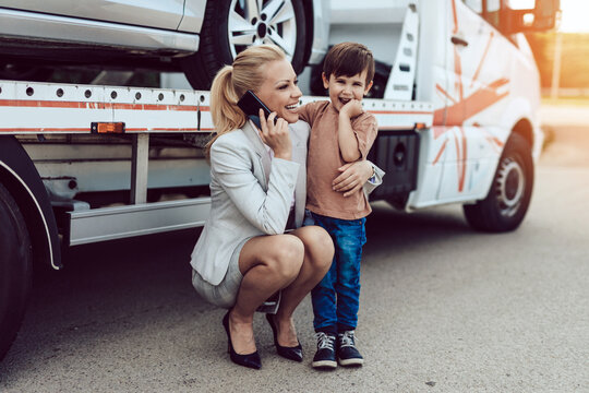 An mother with a small child wait for a tow truck to take away their broken car.