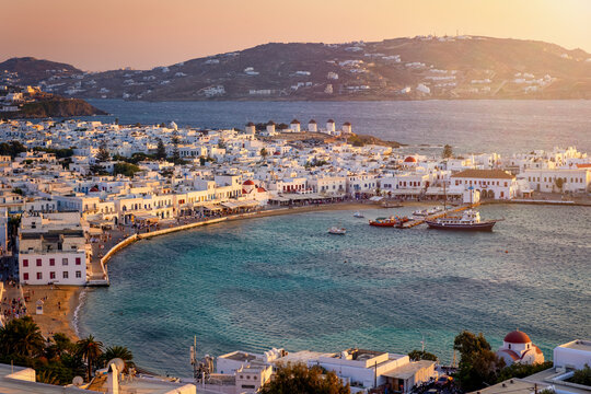 Elevated view of Mykonos island with the old harbour, the famous windmills above and old town during a soft summer sunset, Cyclades, Greece