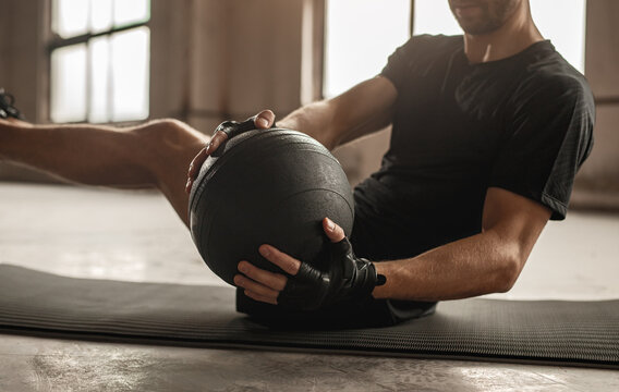 Man doing abs exercise with medicine ball