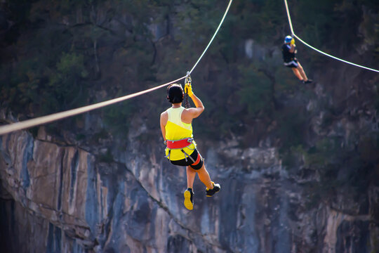 Fun, adrenaline and adventure on the zip line.  Teenager having fun on a zipline on panoramic forest background. Zipline in the forest. People get adrenaline through the zipline in the forest