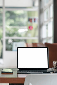 Blank white screen tablet with magic keyboard on wooden table in modern living room.