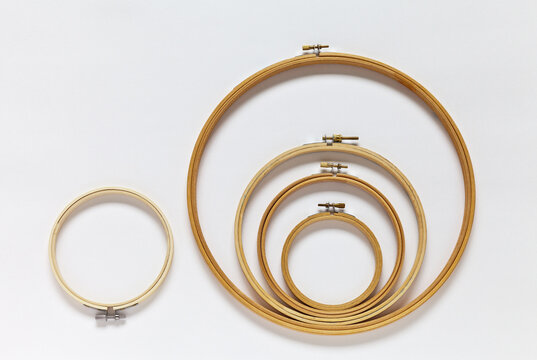 Wooden hoops of different diameters for hand embroidery on white background. Convenient collapsible frames for cross stitching, satin ribbons and long stitch. Embroidery as a hobby. DIY concept