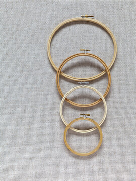 A set of wooden hoops of different diameters for hand embroidery on a background of natural canvas with special square holes. Hobby and crafts. DIY concept. Flat lay, close-up, top view, mock up