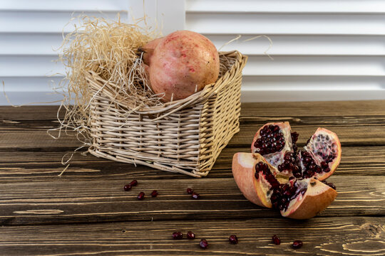 Pomegranates in a basket and on the table on a wooden background.