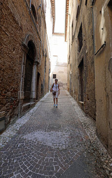 tourist woman walking through the narrow alleys of the ancient city in Italy in summer