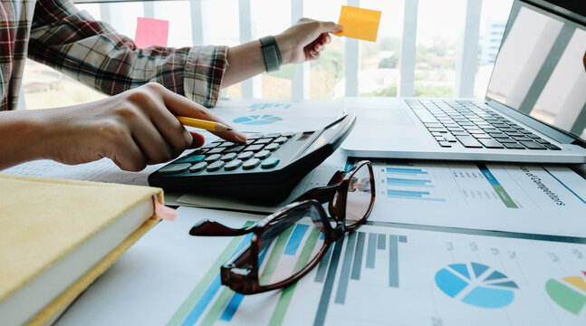 Close up business accounting concept, Business woman using calculator with computer laptop, budget and loan paper in home office