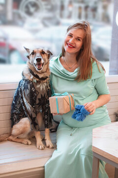 Pregnant woman in blue dress is sitting in cafe with her dog in sweater and holding gift box and blue knitted bootee.