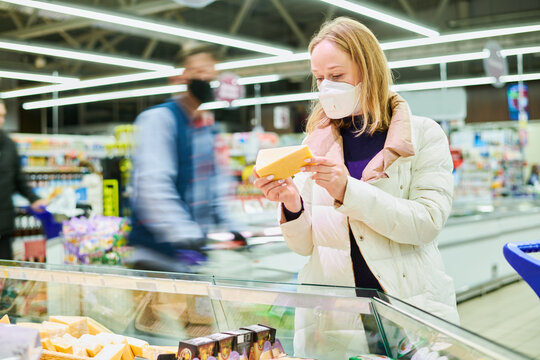 woman in mask buying food in shop at coronavirus epidemic