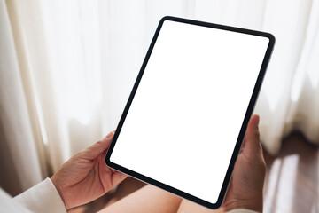Fototapeta Mockup image of a woman holding digital tablet with blank desktop screen at home obraz