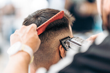 Barber cutting the hair of an adult male with a shaving machine and ca comb