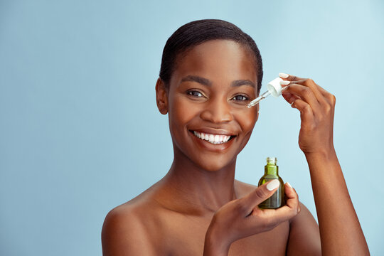 Beauty african woman showing pipette with hydrating facial serum