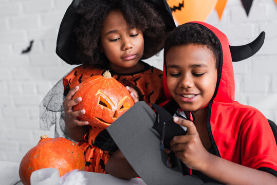 happy african american boy in halloween costume cutting carton with scissors near sister with carved pumpkin