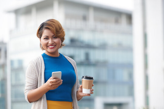 Pretty elegant Asian business lady drinking take out coffee and answering text messages from colleagues