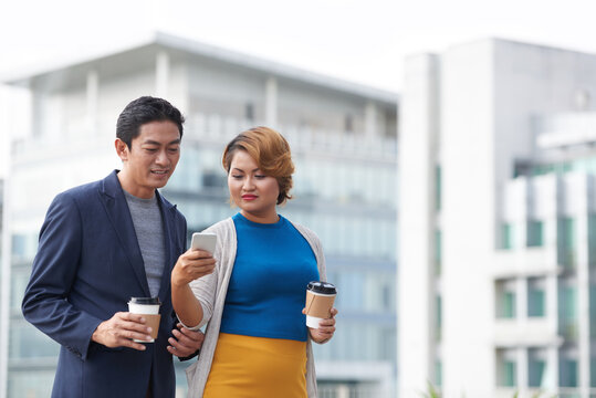 Female entrepreneur showing notification or text message on smartphone to colleague when they are spending time outdoors during coffee break