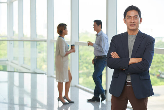 Portrait of confident smiling Vietnamese entrepreneur standing with arms crossed, his colleagues talking in background