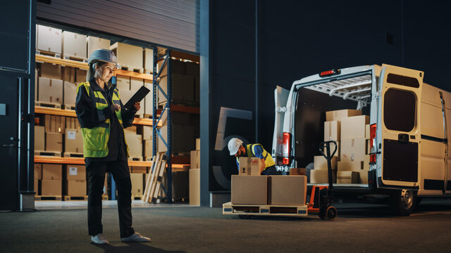 Portrait of Beautiful White Woman Worker Using Tablet Computer in Warehouse full Cardboard Boxes. In Background Professional Loading Cardboard boxes,  e-Commerce Online Orders into Truck.