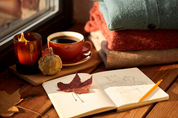 season and objects concept - open sketchbook with drawing of autumn leaf, cup of coffee, wool...