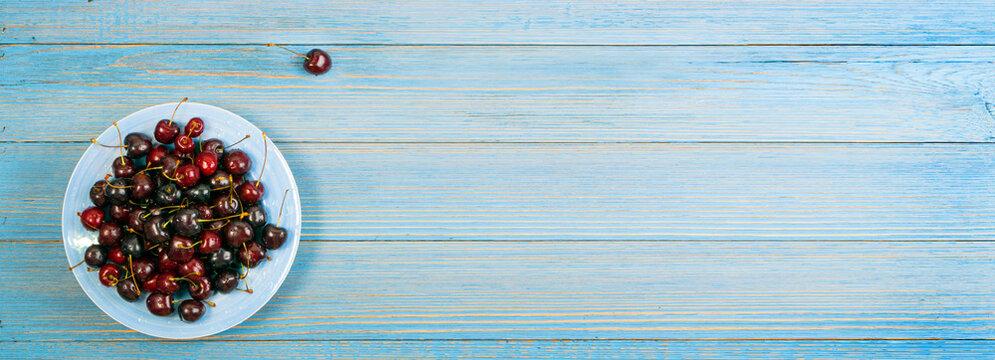 Fresh Overripe ripe Cherries on Blue Rustic Wooden Background