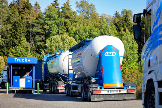 Freight transport trucks stop to refuel at Neste Truck Plus filling station on a sunny afternoon.